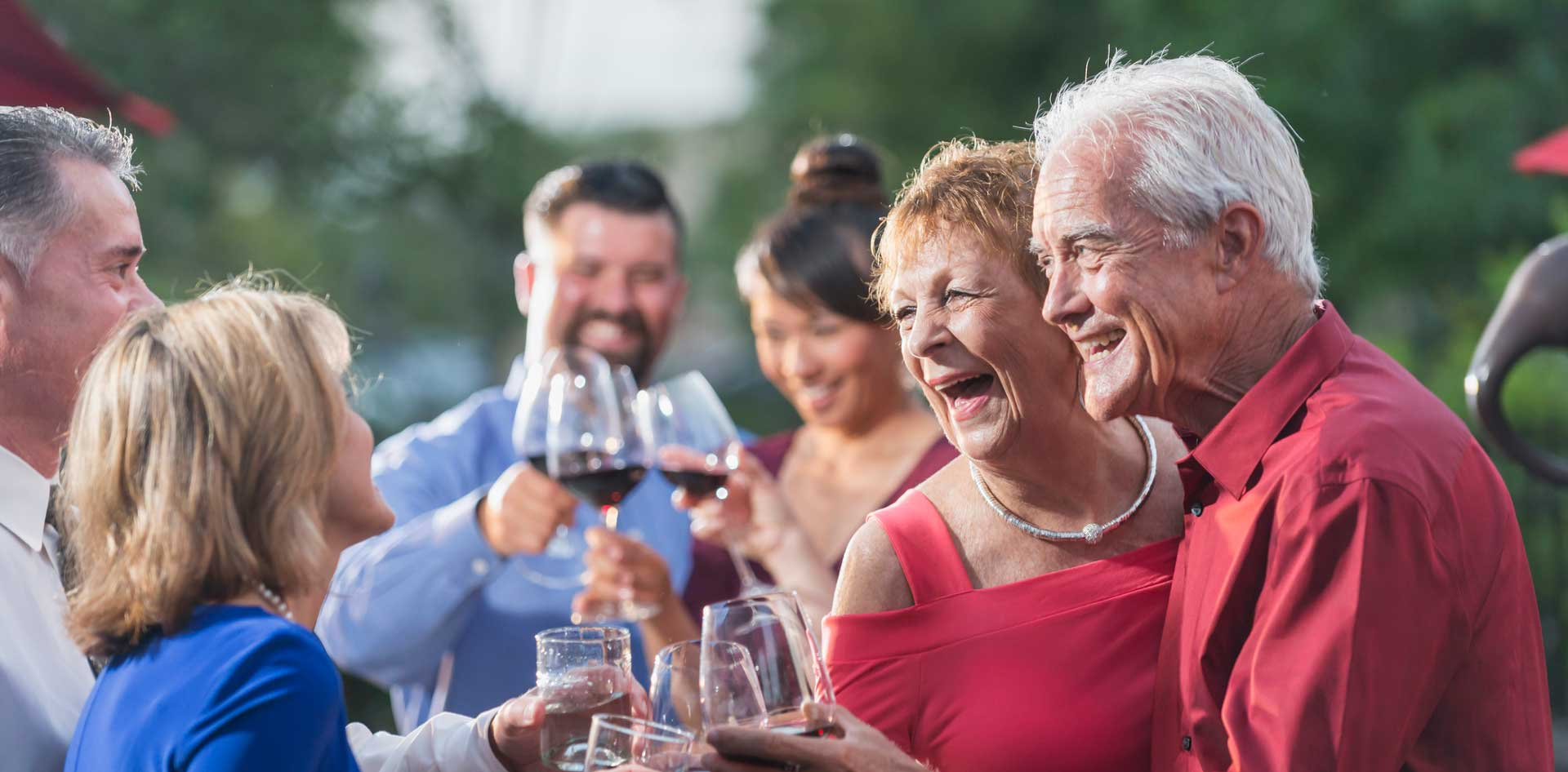 Group of elderly couples laughing and toasting with their wine glasses