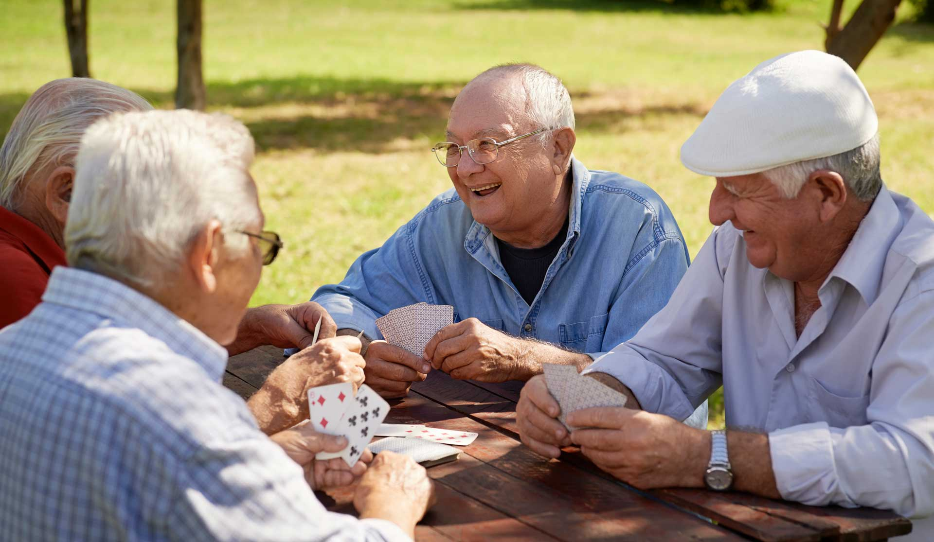 four elderly men playing cards and laughing