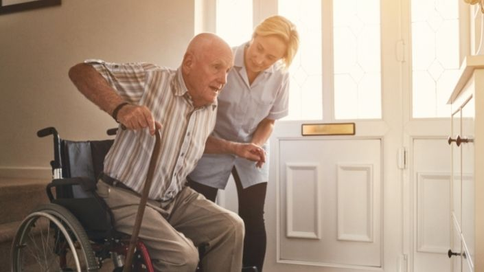 aged care worker helping man out of wheelchair