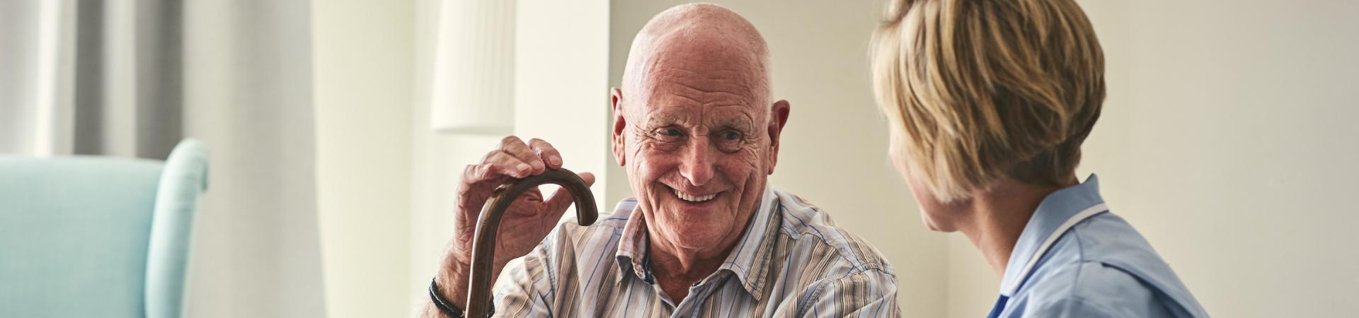 Older man having conversation with carer.