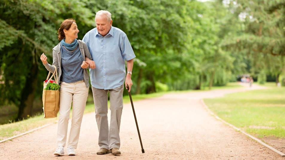 A middle aged woman and an older man with a cane walking arm in arm.