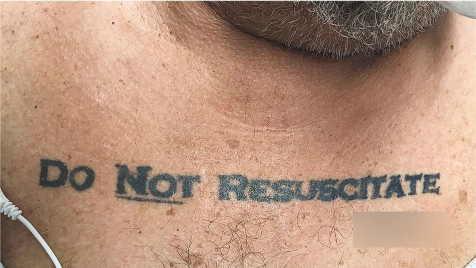 A close up of a man's chest. The text 'Do not resuscitate' is tattooed in big black letters.