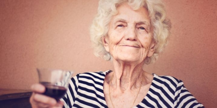 old woman smiling holding wine