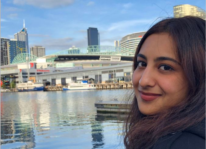 Alina stands by the Yarra River in front of a sports stadium