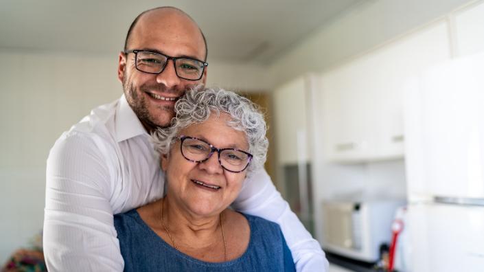 A bald grown up son hugs his mum who has white hair
