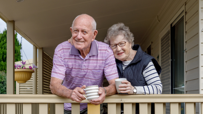 An older couple standing on their verandah holding cups