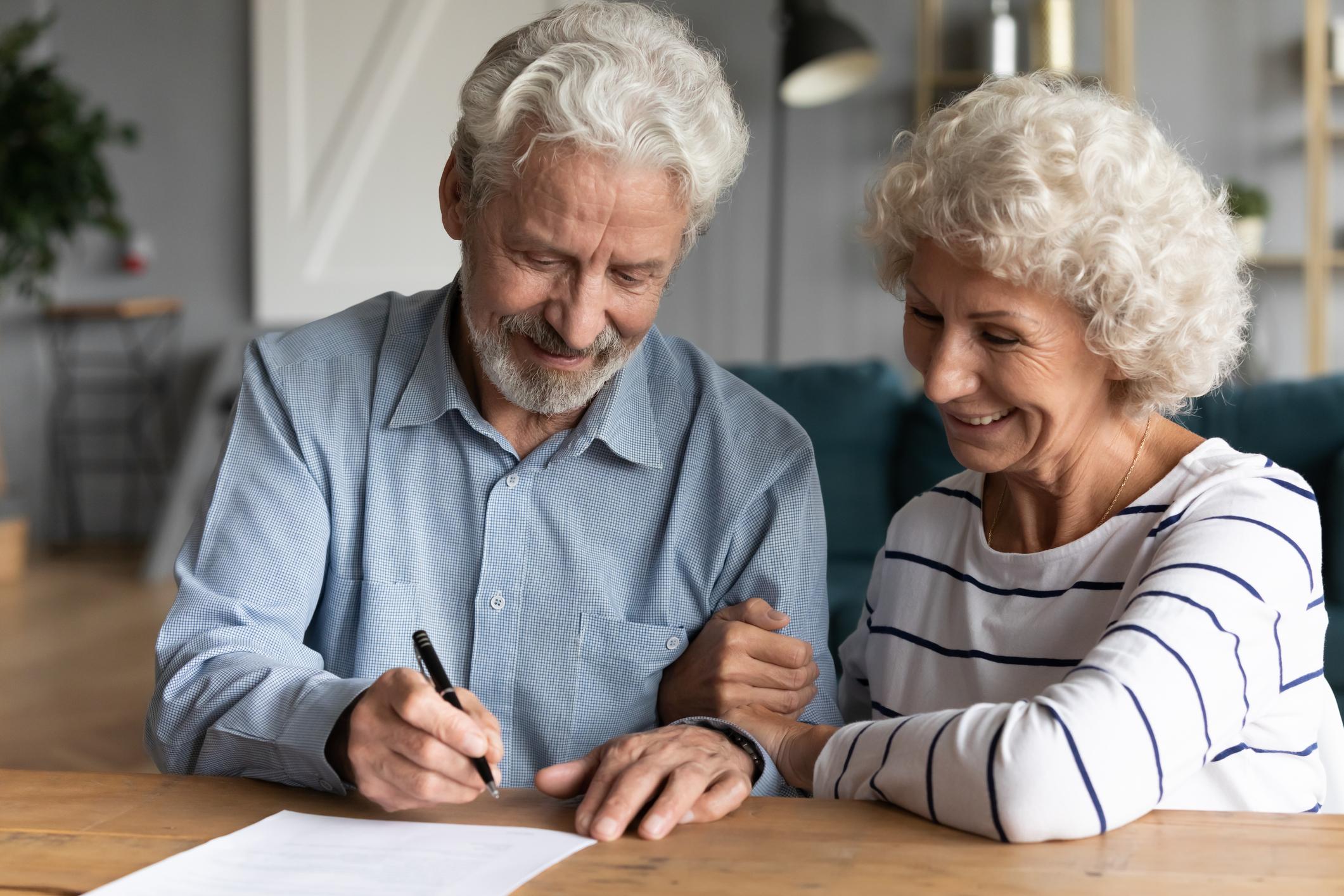 older couple signing paperwork