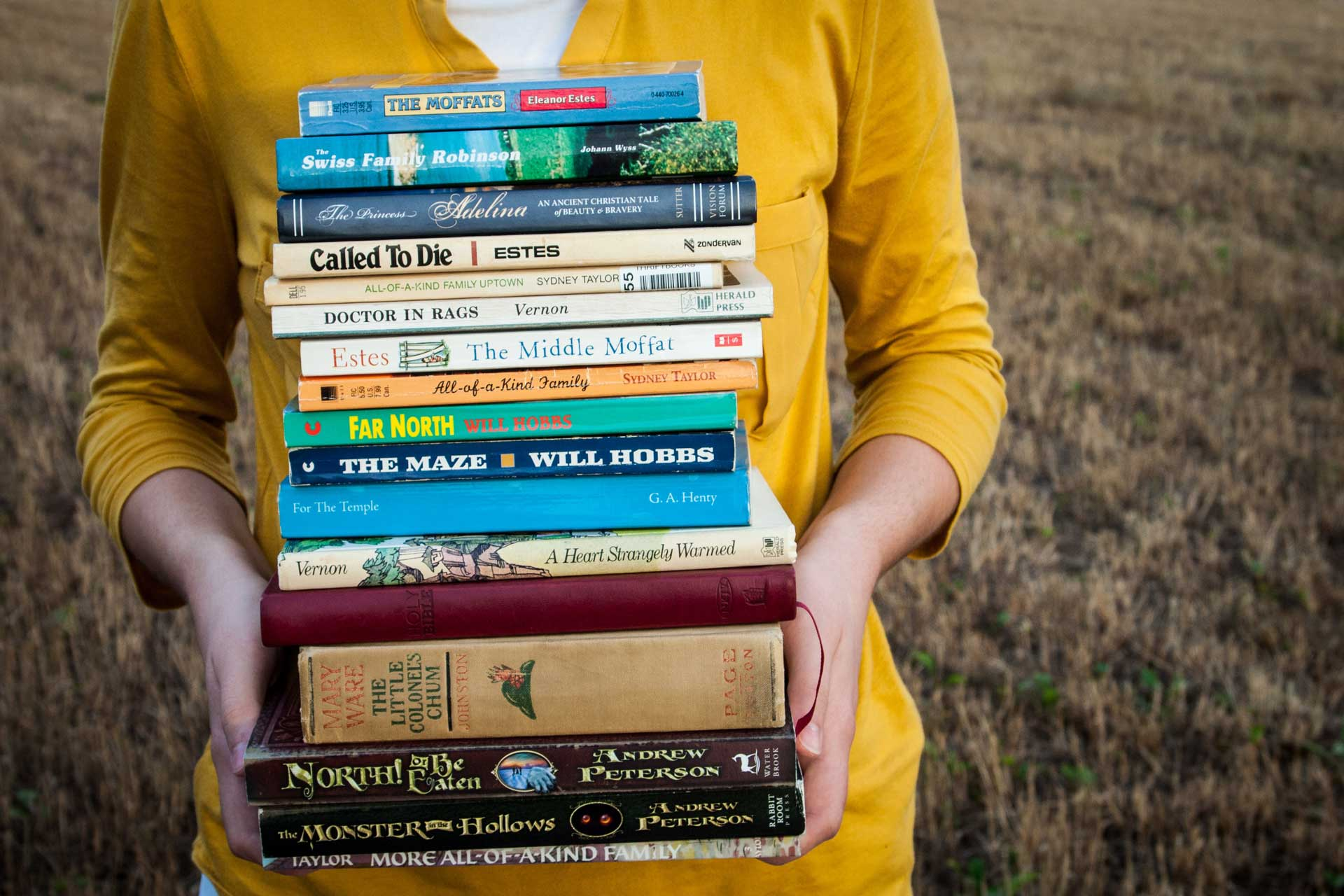 a stack of books held together by a woman in yellow