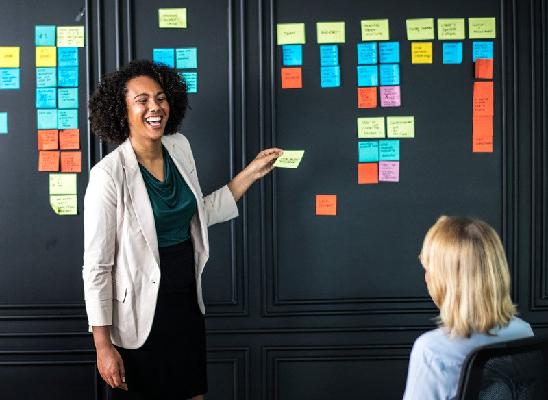 Lady smiling with a board full of post it notes