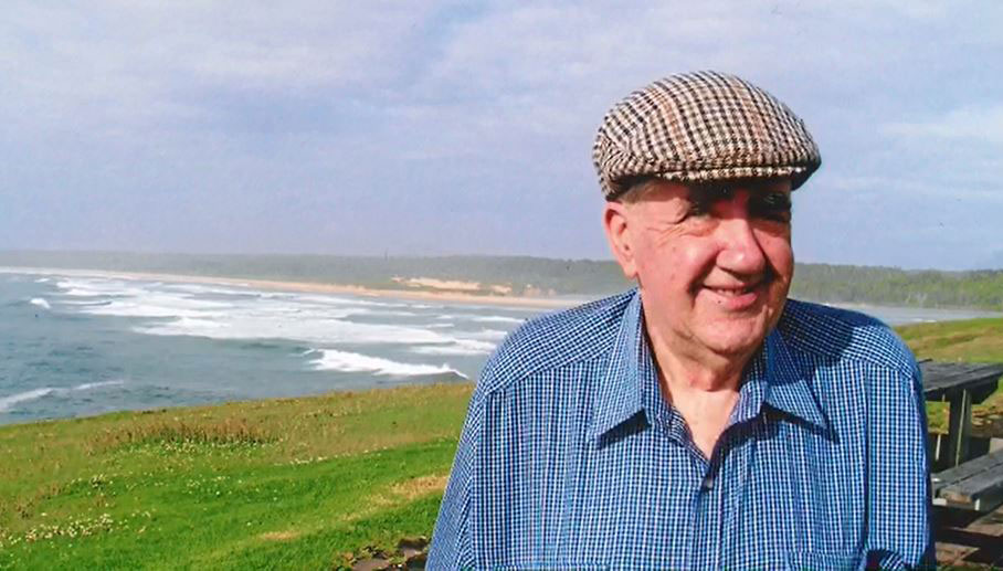 Beach backdrop with an eldery gentlemen with a beret cap and blue collared shirt smiling
