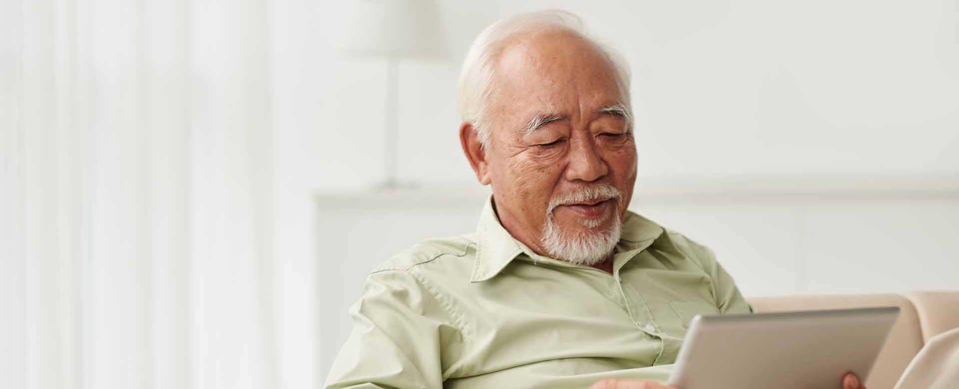 Elderly man browing tablet