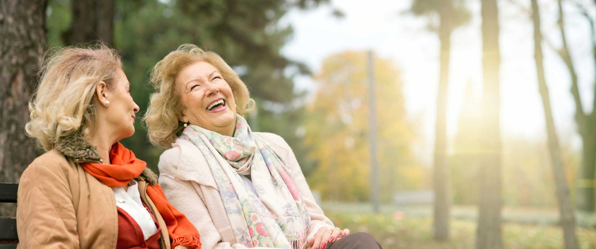 two elderly women at a park laughing