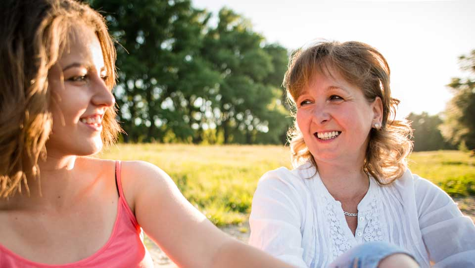candid photo of mother and daughter at the park smiling