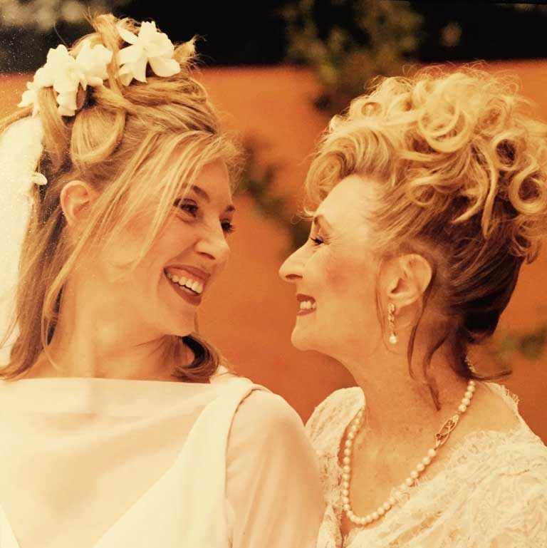blonde haired mother and daughter looking into each other's eyes and smiling. They are both in white dresses and daughter in wedding veil.