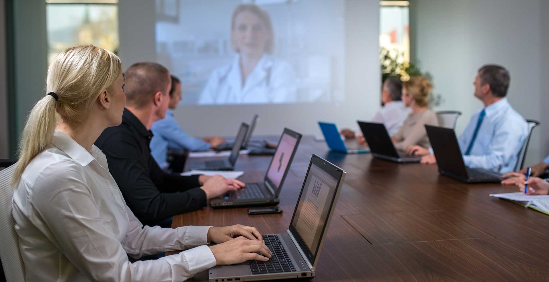 image showing a board room with 8 people with laptops and having a video conference on a large screen in front of them