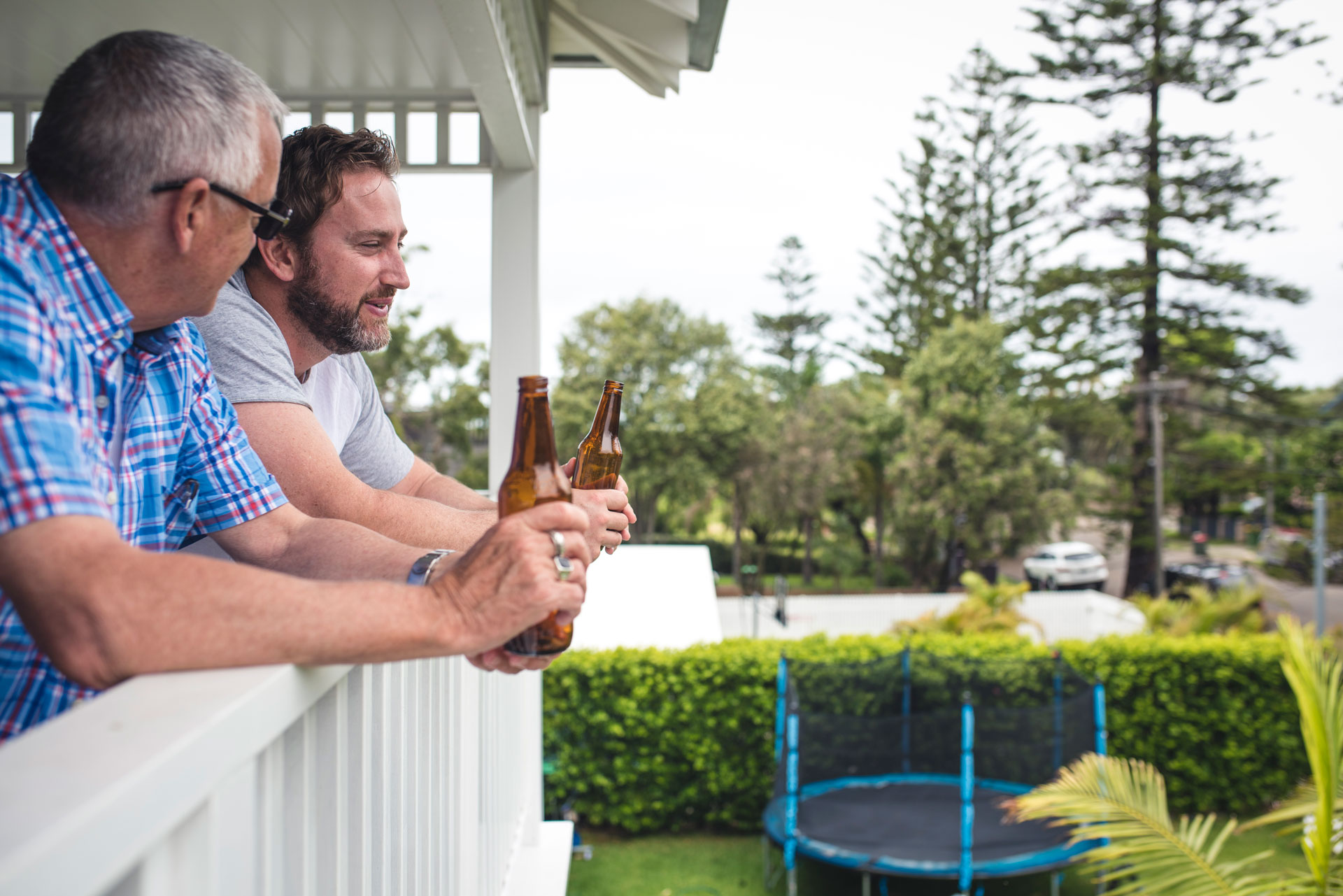 Father and son talking and having a beer on the porch