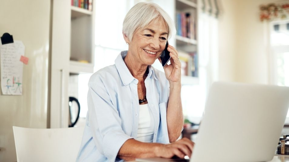 Woman speaking on the phone and typing on laptop