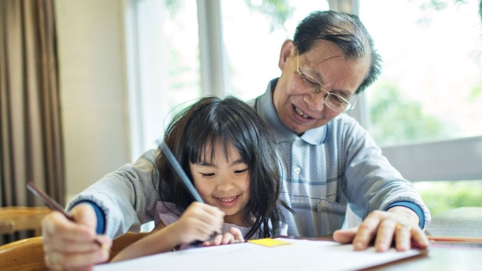 A older man and a young child drawing together.