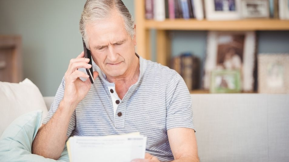 man on telephone looking holding and looking at papers