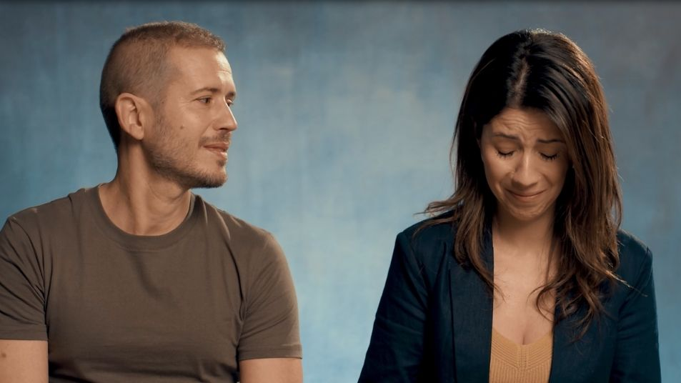 A scene from the video: man looking across at upset woman