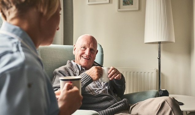 nurse and eldery man having tea in aged care room