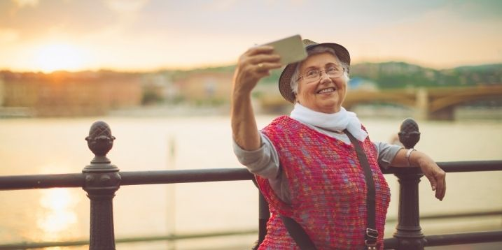 Older woman outdoors smiling taking a selfie