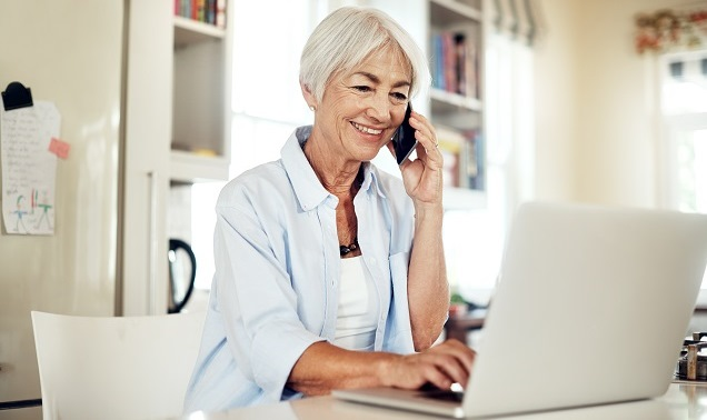 Eldery woman on phone with laptop smiling